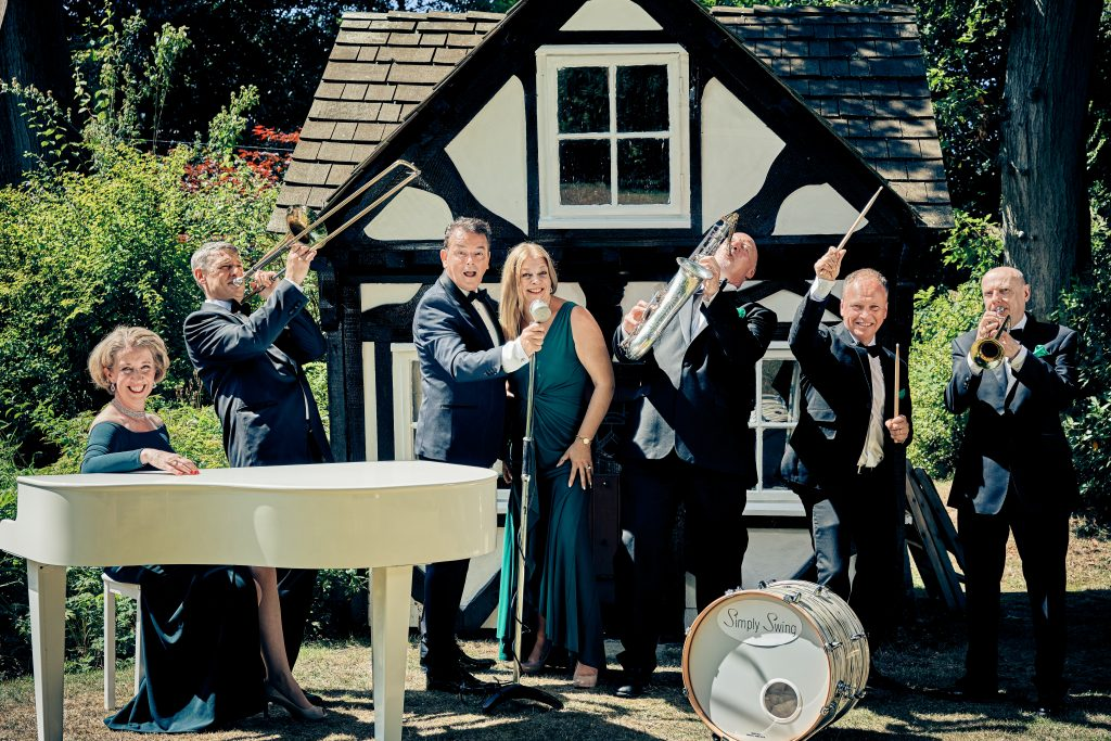 Photo of the Simply Swing Band, Ballroom & Latin American dance singers. A lady at a grand piano, a trombone player, singers, Saxophonist and a drummer